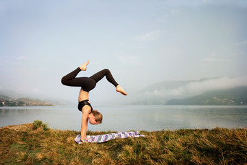 Young woman doing  yoga exercise in morning on  shore of mountain lake. Handstand. Fitness and gymnastic sport outdoor