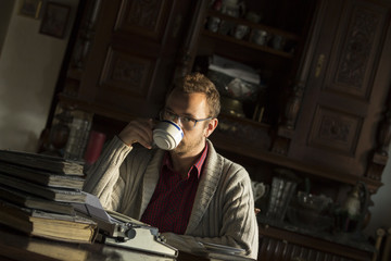 Fototapeta Young man writing on old typewriter.