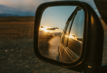 Off-road Car travel by SUV. Mountain Road, clouds and sunset reflecting in rearview mirror. Trip, speed, road