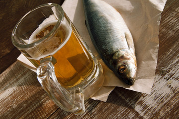 Beer in a glass, a salty herring on paper on a structural wooden table. Beer and snack to beer.
