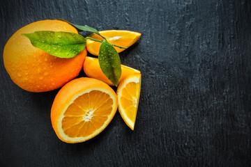 Fresh orange on black stone