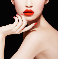 Beautiful skin woman with red lips and nails isolated on black background. Body care, Makeup.