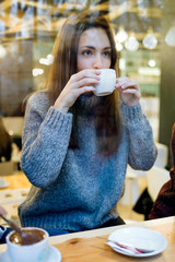 Beautiful young woman drinking coffee at cafe shop.