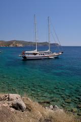 White yacht in a beautiful Aegean bay against blue sky on sunny day in Knidos, Mugla, Turkey.
