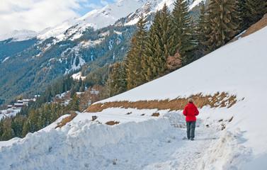 Woman walking through snow in winter