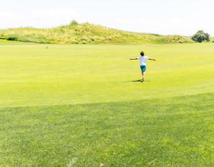 Little kid running on green meadow