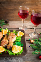 Baked chicken legs on a plate with greens, oranges and cranberries. Christmas decorations