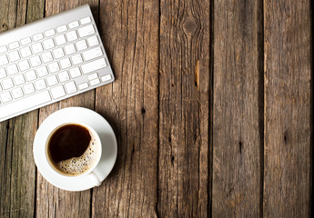 Keyboard, cup of coffee on a wooden background