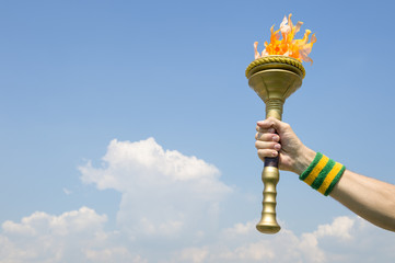 Hand of an athlete wearing Brazil colors sweatband holding sport torch against tropical blue sky