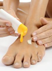 Frau massiert Fuß und Füße mit Hautcreme