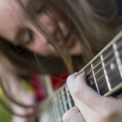 Closeup of girl playing guitar, a blurry picture.