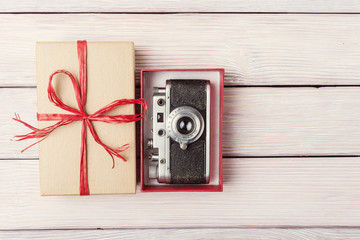 Gift box with retro camera over light wooden background
