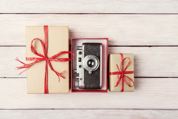 Gift boxes with vintage camera over light wooden background