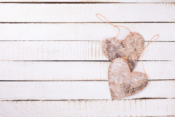 Two decorative hearts on white  painted wooden background.