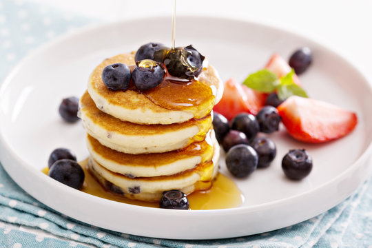 Stack of small pancakes with fresh berries