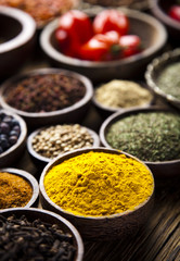 Fototapete - Assortment of spices in wooden bowl background