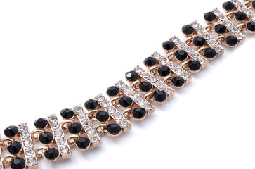gold bracelet with black stones on a white background