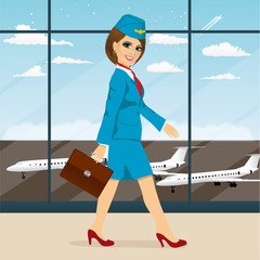 stewardess with briefcase walking through airport terminal