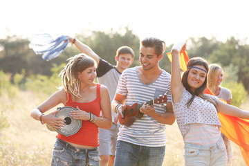 Carefree friends with guitars embraces, outdoors