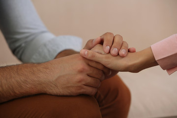 Concept of support - man and woman holding hands in the light room