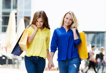 Two beautiful young female friends walking holding hands after s