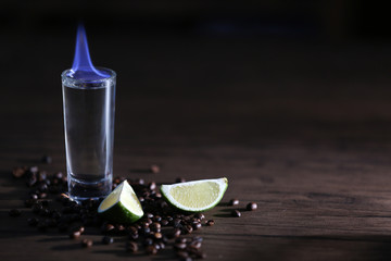 Burning cocktail with lime and coffee beans on wooden background
