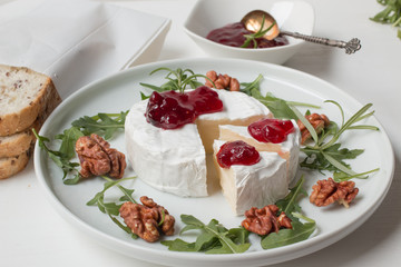 Camembert. Camembert cheese on the plate with cowberry sauce.
