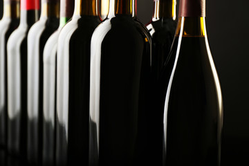 Wine bottles in a row on dark  background, close up