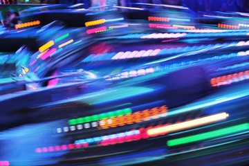 fairground funfair ride background lights moving fast blurred electric neon copy space
