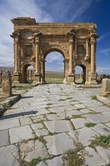 Wall Murals Algeria Algeria. Timgad (ancient Thamugadi or Thamugas). Paving stones of Decumanus Maximus street and 12 m high triumphal arch, called Trajan's Arch