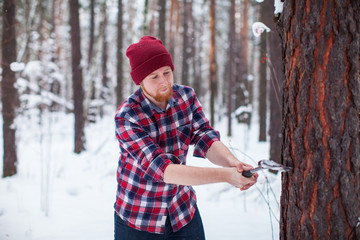 bearded man chopping wood with an hatchet in the winter forest