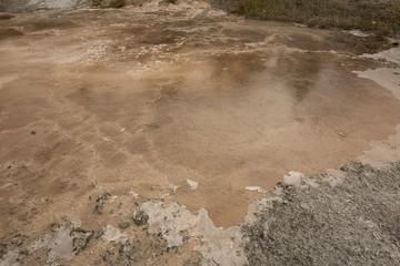 Dark amber geothermal pools over travertine rock, Yellowstone National Park, Wyoming.