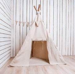wigwam in a room with wooden planked walls