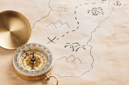 Closeup of compass over stained yellowed paper sheet with part of hand drawn treasure map