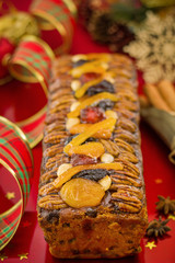 Traditional Christmas fruit cake on red festive background