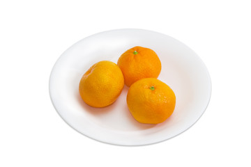 Three mandarin oranges on a white dish