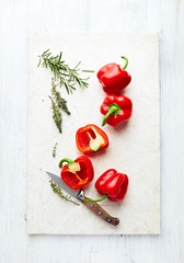 Bell peppers and herbs on a marble chopping board