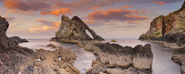 Bow Fiddle Rock, natural arch on Moray coast, Scotland, sunset