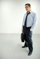 a man in a shirt and tie standing with a briefcase