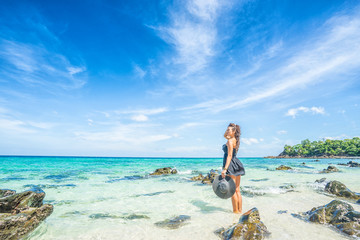 Tropical vacation. Young beautiful woman in black dress and hat on the beach between stones.
