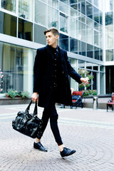 handsome young man in black coat outdoors on building background