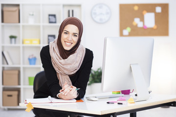 Beautiful Arabic business woman working on computer. Woman in her office, shallow depth of field