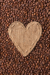 Frame in the shape of heart made of burlap with coffee beans