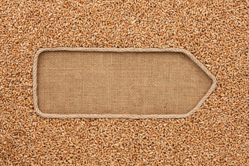 Pointer made from rope with grain wheat  lying on sackcloth