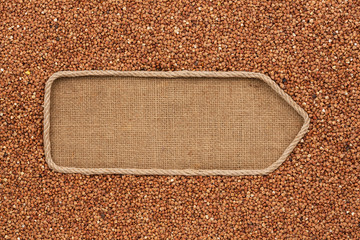 Pointer made from rope with grains buckwheat  lying on sackcloth