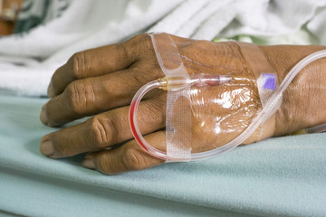 Hand of a old women patient with saline intravenous (IV) drip in