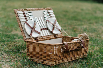 picnic basket full of food and dishes for a perfect picnic in the park