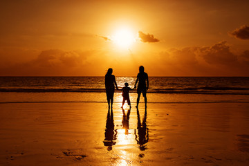 Happy family on a beach at sunrise with child mother and father