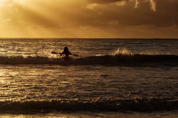 Man in kayak on ocean with big waves at beautiful sunrise