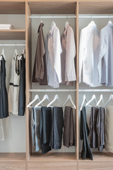 shirts and pants hanging in wooden wardrobe